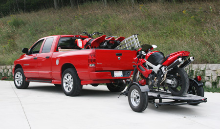 A red pickup truck with a motorcycle trailer behind it