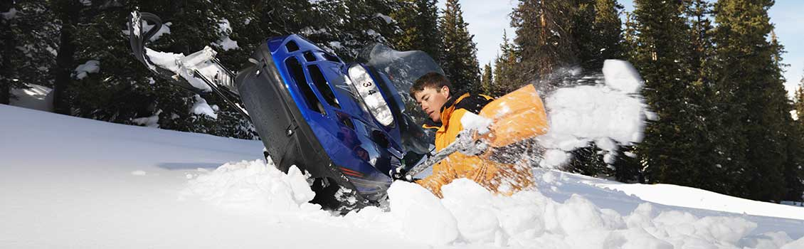 Snowmobiler digging out sled
