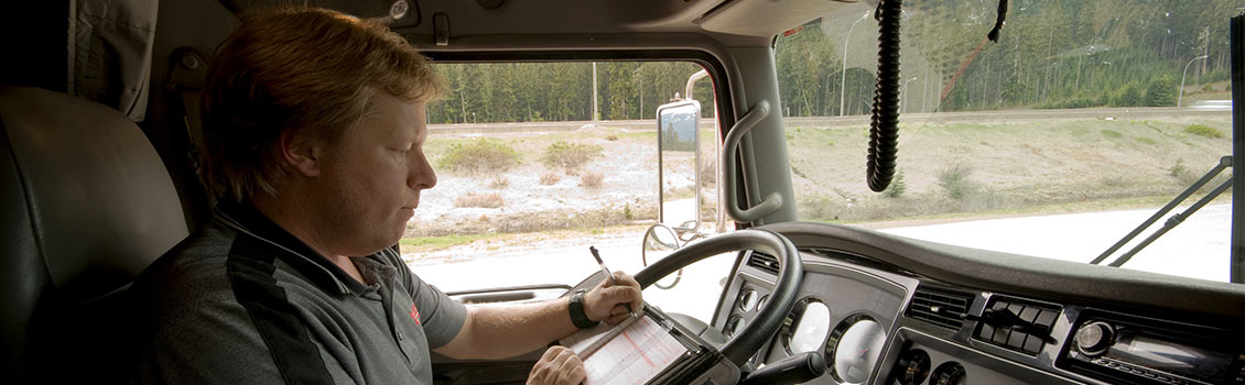 Semi truck driver filling out log
