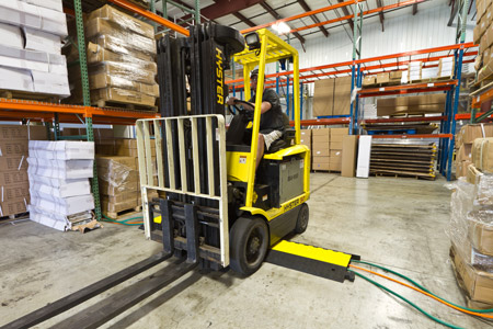 A forklift in a warehouse driving over cable ramps