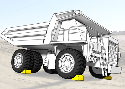 Wheel chocks on each outside tire of a truck weighing over 240 tons