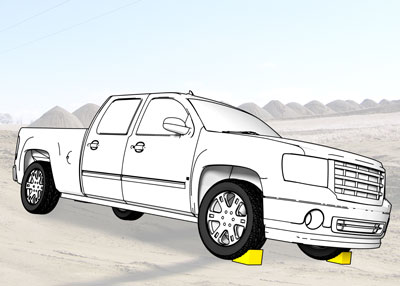 Wheel chocks on each front tire of a pickup truck