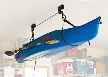A kayak hanging from a garage ceiling via a hoist