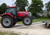 Tractor driving up loading ramps