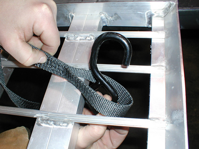 Step 1: After positioning the ramps on the lip of the tailgate or trailer the proper distance apart, locate the point of the ramp where the second rung closest to the tailgate and the center rail meet. Feed the hook end of the safety strap though the strap's looped end, so the strap is wrapped around the center rail below the second rung.