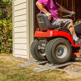 Loading a lawnmower into a shed with the aluminum shed ramps