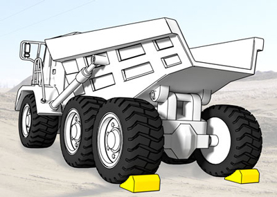 Wheel chocks on each rear tire of an articulated truck