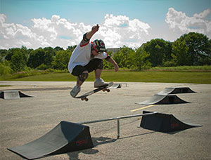 A skateboarder jumping a ramp in a skatepark