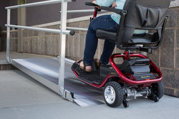 A mobility scooter user riding up a wheelchair ramp